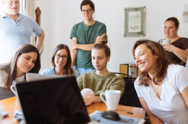 A group of students sitting around a computer working on a group learning exercise.