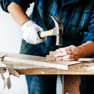 Carpenter showing how to drive a nail.  The picture shows how allowing an employee to show others new skills, the employee's new skill improves, and others learn too.